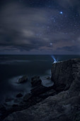 Person shining flashlight at sky at night on coastal cliff, Kauai, Hawaii Islands, USA