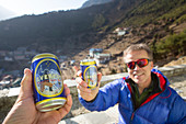 Two hikers drinking a Everest beer on a roof top in Namche Bazar after a long hiking day on the Everest Base Camp trek. The trek to Everest Base Camp (EBC) is possibly the most dramatic and picturesque in the Nepalese Himalaya. Not only will you stand face to face with Mount Everest, Sagarmatha in Nepali language, at 8,848 m (29,029 ft), but you will be following in the footsteps of great mountaineers like Edmund Hillary and Tenzing Norgay. The trek is scenic and offers ever-changing Himalayan scenery through forests, hills and quaint villages. A great sense of anticipation builds as you trek