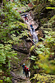 Canyoning in narrow gorge filled with rapids, pools and waterfalls in Soca valley near Bovec, Slovenia