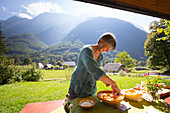 A woman (farmer) is preparing a lunch table with local food products at agritourism and cheese farm Cernuta in the Soca valley near the town of Bovec with views on the Mangart mountain peaks of Slovenia.