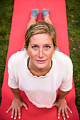 A young athletic blonde woman in her twenties enjoying yoga on a bright red mat in the grass and looking at camera, Jackson, Wyoming, USA
