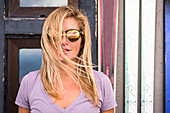 A young athletic blonde woman in her twenties wearing hip sunglasses outside Corbett's Cabin in Wyoming on a windy day.