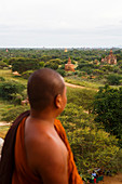 Buddhist monk looking at temples of Bagan, Mandalay Region, Myanmar. The area has over 2, 000 ancient temples and is one of the most popular tourist destinations in Myanmar.
