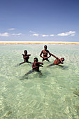 Four boys posing together in coastal water, Mozambique