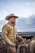Portrait of rancher horseback riding against clouds, Oregon, USA
