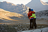 A couple watches sunrise over the mountains from the Puppet Lake Basin on a two-week trek of the Sierra High Route in the John Muir Wilderness in California. The 200-mile route roughly parallels the popular John Muir Trail through the Sierra Nevada Range of California from Kings Canyon National Park to Yosemite National Park.