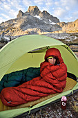 Backpacker in her sleeping bag on cold morning at camp near Thousand Island Lake with Banner Peak in background on trek of Sierra High Route in Minarets Wilderness, Inyo National Forest, California, USA