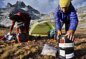 Backpackers pack up camp near Thousand Island Lake with Banner Peak in background on two-week trek of Sierra High Route in Minarets Wilderness, Inyo National Forest, California