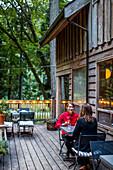 Two women sitting in patio of restaurant, Galiano Island, British Columbia, Canada