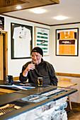 Older man enjoying beer beside counter at pub, Scotland, UK