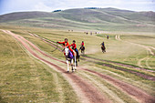 Riders from age of 5 to 12 years of age wear vibrantly color stain capes and matching suits, participate in bareback horse races of distance of 20 kilometers. Some only wear socks to cut down the weight of bulky boots and almost all have a dashur a crop to urge their horses on. Naadam Festival at Bunkhan Valley, Mongolia.