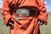 Mid section of mongolian man wearing deel, national dress of Mongolia, tied with leather belt with big silver buckle, Naadam Festival, Bunkhan Valley, Bulgam, Mongolia