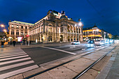 Illuminated exterior of Vienna State Opera across street at night, Vienna, Austria