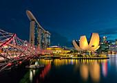 Helix Bridge and illuminated building of ArtScience Museum at night, Singapore