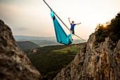 Highline athlete walking on slackline in mountains while his fellow hanging in hammock, Tijesno Canyon, Banja Luka, Bosnia