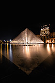 Illuminated pyramid in the Louvre at night, light reflections in the fountain basin in front of the glass pyramid, Île-de-France, Paris, France