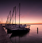Jetty with sailboats at sunset at Ammersee, Voralpenland, Bavaria, Germany