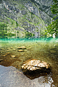 Reflection at Obersee with rock stone in the water in the background. Rocky mountain wall, Berchtesgaden National Park, Bavaria, Germany