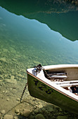 Bow of rowboat on the Sylvensteinsee, mirroring mountains in the upper edge, Lenggries, Bavaria, Germany