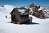 Old wooden hut in the snow overlooking the Passo di Giau where the snow melts and releases the mountains, Dolomites, Cortina d'Ampezzo, Belluna, Italy