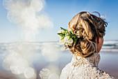 Blonde Braut mit Blumen im Haar am sonnigen Strand