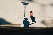 Junge Frau mit Smartphone auf Betonmauer sitzend
