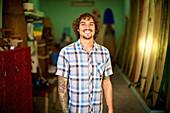 Portrait confident, happy male surf shop owner