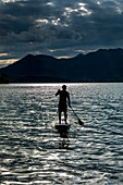 Silhouette man paddleboarding on sunny, idyllic lake, Walchensee, Bavaria, Germany