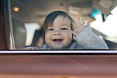 Smiling baby girl behind car window