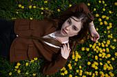 Junge Frau in braunem Blazer liegt auf Wiese mit gelben Blumen