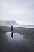Man wearing blue coat on black sand beach in Kirkjub?jarklaustur, Iceland