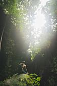 Mann mit Rucksack sitzt auf Felsen unter Bäumen auf Bali, Indonesien