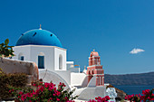 The pink chapel next to the blue dome in Oia, Santorini, Greece