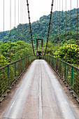 An adventurously narrow bridge over the Pastaza River near Baños, Ecuador. The bridge is approved for cars