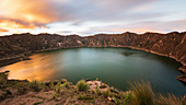 A sunset at the edge of the crater lake Quilota in Ecuador