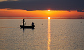 A sunset in Marsala, Sicily with a fishing boat and two fishermen in the foreground