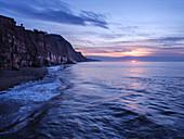 Sun peeps below a cloud bank at Sidmouth, Devon, England, United Kingdom, Europe