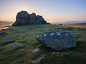 Sun behind granite rocks at Haytor in Dartmoor National Park and distant mist in the Teign Valley, Bovey Tracey, Devon, England, United Kingdom, Europe