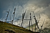 Prayer flags commemorating a deceased, imprinted with the mantra Om Mani Padme hum, with dark clouds and mountains in the, Phobjikha Valley, Bhutan, Himalayas, Asia