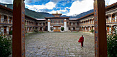A nun in the courtyard of the Pema Choling Nunnery, Tang Tal, Bumthang, Bhutan, Himalayas, Asia
