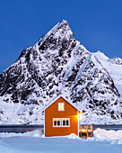 Yellow rorbuer hut in the snow at twilight, Sakrisoy, Moskenesoya, Lofoten Islands, Nordland, Norway, Europe