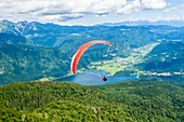 Paraglider sails over Lake Bohinj and its mountains, Slovenia, Europe