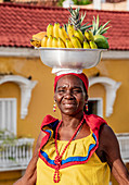 Colourful Palenquera selling fruits on the walls of Cartagena, Bolivar Department, Colombia, South America