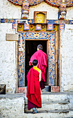 Asian monks walking in temple doorway, Bhutan, Kingdom of Bhutan