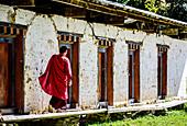 Asian monk walking by monastery doors, Bhutan, Kingdom of Bhutan