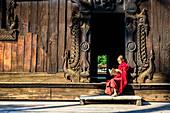 Asian monk reading by ornate doorway to temple, Myanmar