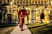 Asian man carrying umbrella by ornate temple, Myanmar