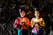 Asian girls holding candles in temple, Myanmar
