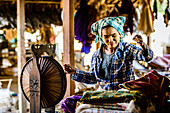 Asian woman spinning thread, Myanmar