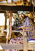 Asian girl weaving fabric, Myanmar